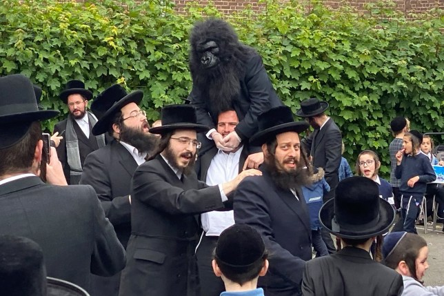 ALL ROUND PICTURES STANDARD RATES ONLINE AND PRINT The Jewish community in Stamford Hill pictured here ignoring social distancing rules while celebrating Lag BaOmer a festive day on the jewish calendar. around 300 people gathered together in dancing together in a small estate. One man was seen dressed as a Gorilla whilst sitting on the shoulders of another man. BYLINE MUST READ KPPICS.CO.UK