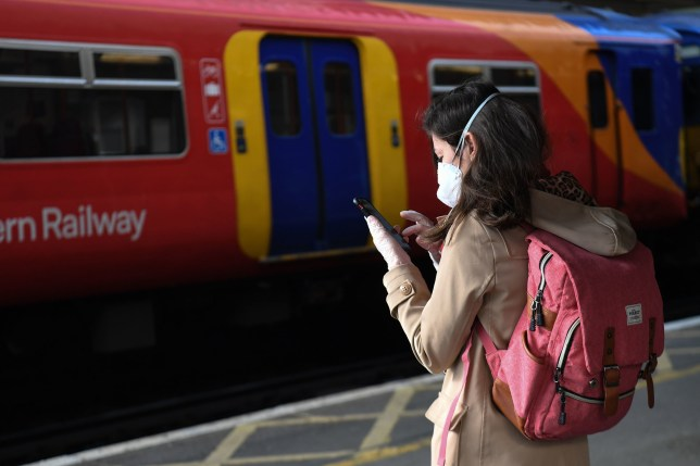A passenger waits to board a train at Clapham Junction station in London, after the announcement of plans to bring the country out of lockdown. PA Photo. Picture date: Wednesday May 13, 2020. See PA story HEALTH Coronavirus. Photo credit should read: Kirsty O'Connor/PA Wire