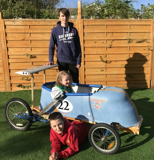 siblings show off the bathtub they used to make a go-kart