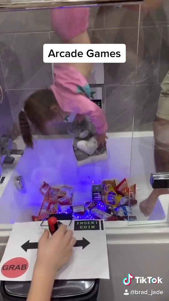 Video from the hilarious video shows a dad recreating an arcade claw 'grabber' machine at home - using his daughter, an adapted bin and the BATH.