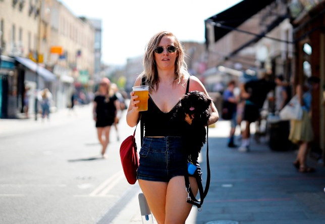 People enjoy the sunshine in Broadway Market, Hackney, north east London on May 20, 2020, the hottest day of the year so far