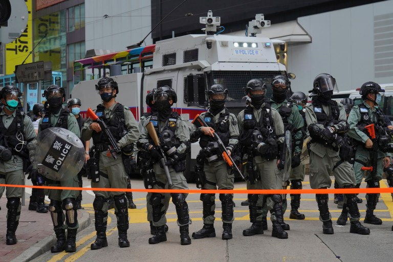 Riot police stand in formation in front of water cannon tuck during a protest against Beijing's national security legislation in Causeway Bay in Hong Kong, Sunday, May 24, 2020. Hong Kong police fired volleys of tear gas in a popular shopping district as hundreds took to the streets Sunday to march against China's proposed tough national security legislation for the city. (AP Photo/Vincent Yu)