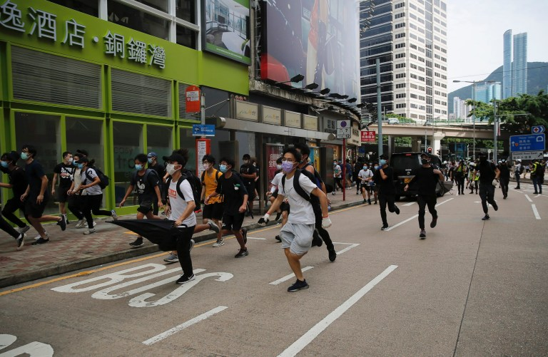 Protesters run as they are chased by police during a protest against Beijing's national security legislation in Causeway Bay in Hong Kong, Sunday, May 24, 2020. Hong Kong police fired volleys of tear gas in a popular shopping district as hundreds took to the streets Sunday to march against China's proposed tough national security legislation for the city. (AP Photo/Kin Cheung)