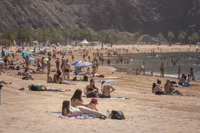 People sunbathe at Las Teresitas beach in Tenerife