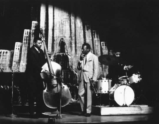 Jazz trumpeter Miles Davis performs onstage with his bass player Paul Chambers and drummer Jimmy Cobb