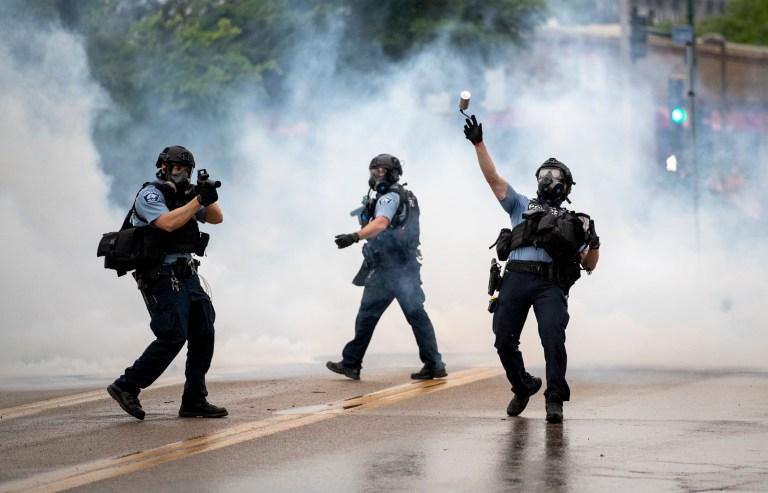Un officier de police jette une cartouche de gaz lacrymogène contre les manifestants au 3e commissariat de police de Minneapolis, à la suite d'un rassemblement pour George Floyd le mardi 26 mai 2020, à Minneapolis