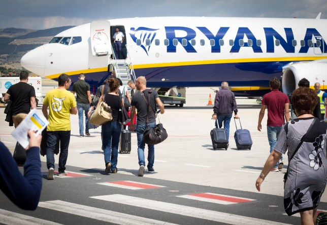 Passengers on the tarmac at Comiso Airport in Sicily walking with carry-on luggage toward a Ryanair airplane. Ryanair is the worst airline for coronavirus refunds, a survey has found.