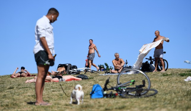 People enjoy the warm weather at a park in London