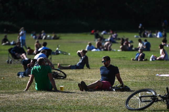 People are seen drinking takeaway pints from a pub on Wandsworth Common