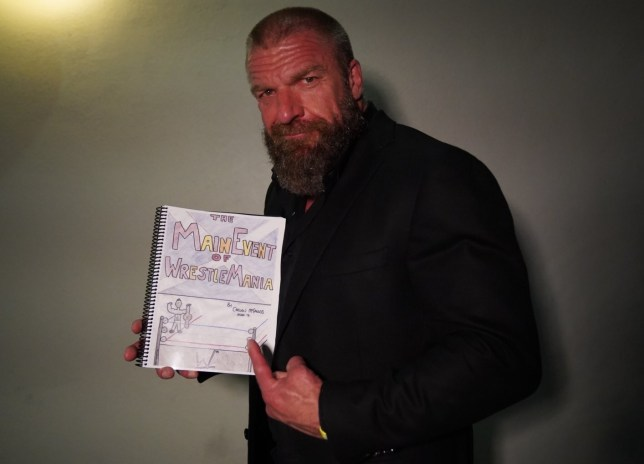WWE superstar Triple H with Caelan McFaulds' Main Event of WrestleMania NHS fundraiser book