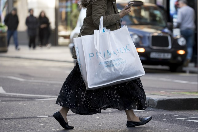 The bottom half of a woman, carrying a Primark bag and wearing a long skirt and flats