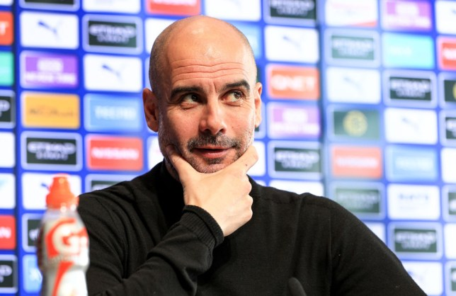 Pep Guardiola smirks in a Manchester City Press Conference