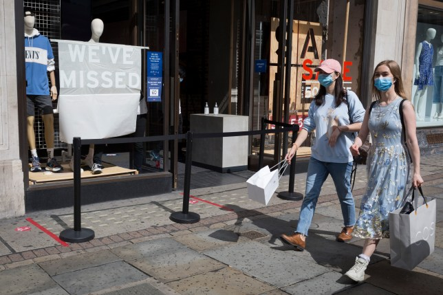 two young women wearing face coverings walk past an employee of a Levis shop on Regent Street.