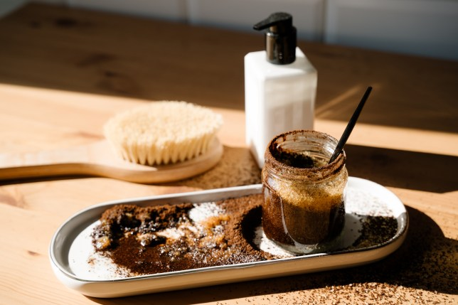 A set of a brush, lotion and a pot of homemade coffee scrub