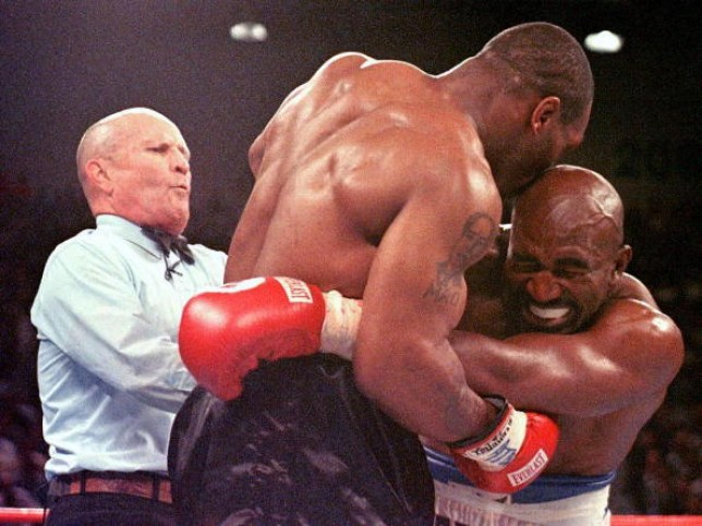 Mike Tyson bites into Evander Holyfield's ear during their 1997 fight