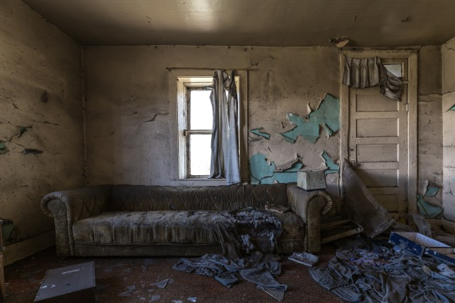 The inside of a rundown abandoned house with a sofa in the room and wallpaper peeling off the walls