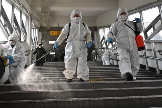 Des travailleurs portant un équipement de protection désinfectant en spray pour aider à prévenir la propagation du coronavirus COVID-19, dans une station de métro à Séoul le 13 mars 2020. - La Corée du Sud - autrefois la plus grande épidémie de coronavirus en dehors de Chine - a vu ses patients nouvellement rétablis dépasser de nouvelles infections pour la première fois le 13 mars, car il a signalé son plus faible nombre de nouveaux cas depuis trois semaines. Le Sud a confirmé 110 nouveaux cas, portant le total à 7 979.