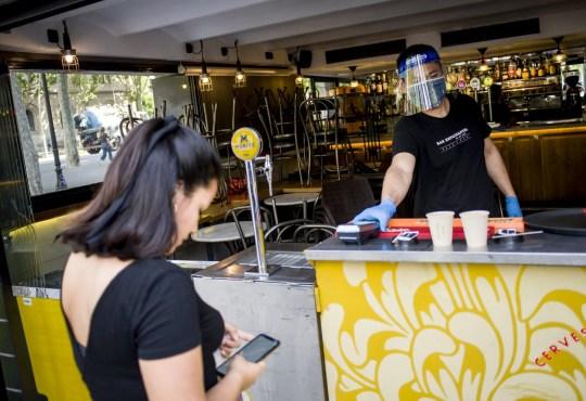 Crédit obligatoire: Photo par Jordi Boixareu / ZUMA Wire / REX (10657608h) Un serveur portant un masque facial et un écran facial protecteur assiste un client dans un bar de Barcelone. Barcelone et sa zone métropolitaine entrent dans la phase 1 du processus de désescalade du verrouillage des coronavirus à partir de ce lundi, les terrasses des bars et restaurants peuvent s'ouvrir à la moitié de leur capacité après 2 mois de fermeture. COVID-19: RECUPERATION: Barcelone entre dans la phase 1, Catalogne, Espagne - 25 mai 2020