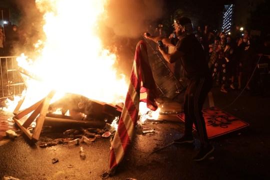 WASHINGTON, DC - 31 MAI: Des manifestants ont mis le feu et brûlé un drapeau américain lors d'une manifestation près de la Maison Blanche le 31 mai 2020 à Washington, DC. L'officier de police de Minneapolis, Derek Chauvin, a été arrêté pour la mort de Floyd et est accusé de s'agenouiller sur le cou de Floyd alors qu'il le suppliait de ne pas pouvoir respirer. Floyd a été déclaré mort peu de temps après. Chauvin et trois autres officiers, qui étaient impliqués dans l'arrestation. (Photo par Alex Wong / Getty Images)