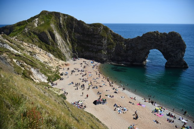 People enjoy the warm weather on the beach at Durdle Door, near Lulworth, in Dorset, after the public were reminded to practice social distancing following the relaxation of coronavirus lockdown restrictions in England. PA Photo. Picture date: Monday June 1, 2020. Councillor Vikki Slade, the leader of Bournemouth, Christchurch and Poole Council, has written to local MPs and the chief constable of Dorset Police after widespread scenes of irresponsible behaviour witnessed across the area???s beaches, including at the limestone arch of Durdle Door where three people were seriously injured after jumping off cliffs into the sea. See PA story POLICE DurdleDoor. Photo credit should read: Kirsty O'Connor/PA Wire