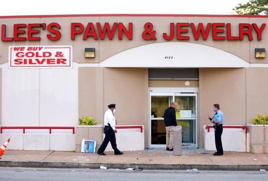 La police enquête sur la scène d'une fusillade sur Lee's Pawn & Jewelry à Saint-Louis, le mardi 2 juin 2020. Un policier retraité de 77 ans de Saint-Louis, qui a purgé 38 ans au sein de la force, a été abattu par des pillards à mardi matin, a annoncé la police. David Dorn a été retrouvé mort sur le trottoir devant Lee's Pawn & Jewelry, qui avait été saccagé après que les protestations pacifiques contre la mort de George Floyd soient devenues violentes du jour au lendemain. (David Carson / St. Louis Post-Dispatch via AP)