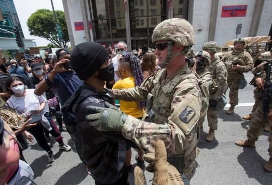 Des manifestants saluent un membre de la Garde nationale après une prière lors d'une manifestation contre la mort de George Floyd, le mardi 2 juin 2020, dans la section hollywoodienne de Los Angeles. Floyd, un Noir, est décédé le 25 mai après avoir été retenu par des policiers de Minneapolis (AP Photo / Ringo H.W. Chiu)