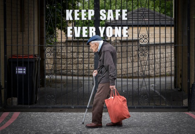 A pensioner walks past a sign that reads 'Keep Safe Everyone'