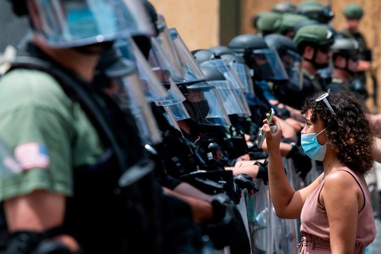 Un manifestant montre une photo de George Floyd depuis son téléphone portable contre un mur d'agents de sécurité alors qu'elle et d'autres manifestent sa mort près de la Maison Blanche le 3 juin 2020, à Washington, DC. - Les États-Unis ont éclaté en jours et nuits de protestations, de violences et de pillages, à la suite du décès de George Floyd après qu'il ait été détenu et maintenu par un genou jusqu'au cou, mourant peu après. (Photo par JIM WATSON / AFP) (Photo par JIM WATSON / AFP via Getty Images) *** BESTPIX ***