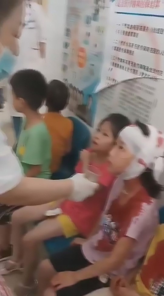 Pic Shows: Injured primary pupils fill a local hospital in Wuzhou, Guangxi, after a stabbing incident which left 40 staff and children injured; This distressing footage shows bandaged primary pupils filling a hospital waiting area after a school security guard went on a hacking spree injuring around 40 children and staff.