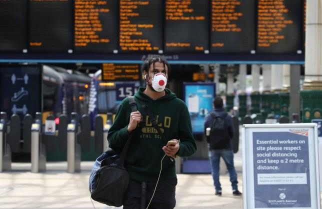 A rail passenger wearing mask at Edinburgh Waverley Station