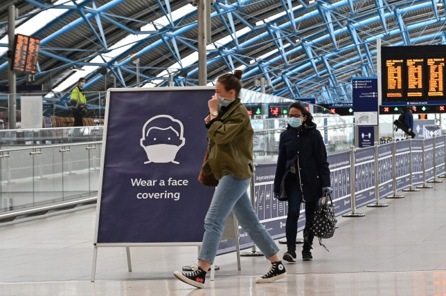 a sign tells passengers to cover their faces