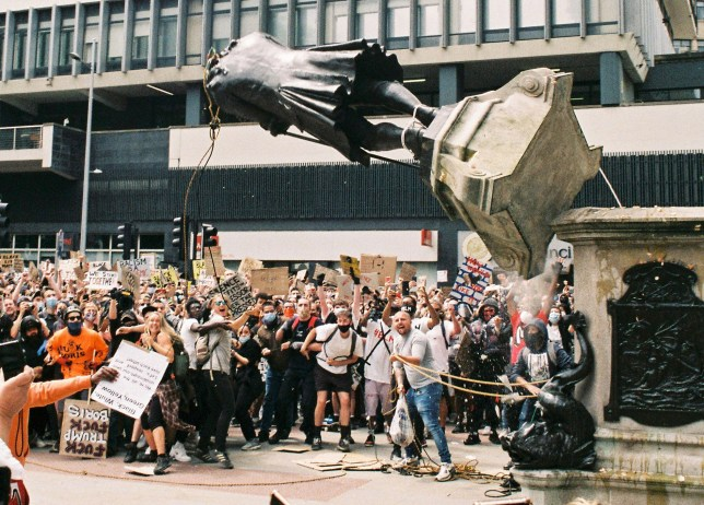 The dramatic moment that the statue of Edward Colston was pulled from its plinth in Bristol city centre, June 7 2020. The new photo which has emerged today was captured on film by Harry Pugsley who was delighted to see hed captured the iconic image when the film was returned from the developers. See SWNS story SWBRhistory. The Colston statue will be placed in a museum it was confirmed today - as a new picture of the historic moment it came crashing down emerged. Mayor of Bristol Marvin Rees said today the bust will be fished out and put on display locally. He also revealed that historians and local experts will be commissioned to ''look into the city's past''. Mr Rees said ''Bristol???s true history will be researched by a new commission so the city can better understand its story''.