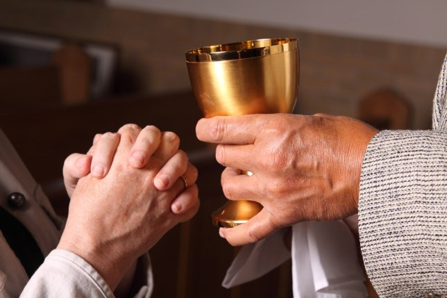 Holy communion in a church as a priest passes a cup of wine.