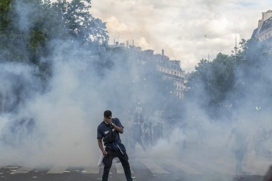 Un homme couvre ses yeux au milieu d'un nuage de gaz lacrymogène déployé lors d'une manifestation contre le racisme le 13 juin 2020 à Paris, en France.
