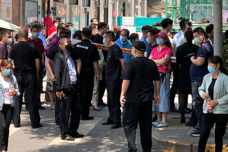 The Police and security officials watch as people gather on a coronavirus test centre at a sports centre in Beijing, Tuesday, June 16, 2020. China has reported dozens of more coronavirus infections Tuesday that it passes the tests and the locking of the measures in the neighbourhoods of the capital for control of what seemed to be its largest outbreak in more than two months. (AP Photo/Mark Schiefelbein)