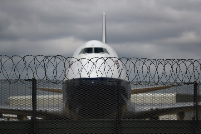Razor wire sits on a security fence near a passenger aircraft, operated by British Airways, a unit of International Consolidated Airlines Group SA (IAG) grounded at London Heathrow Airport in London, U.K., on Monday, June 8, 2020.