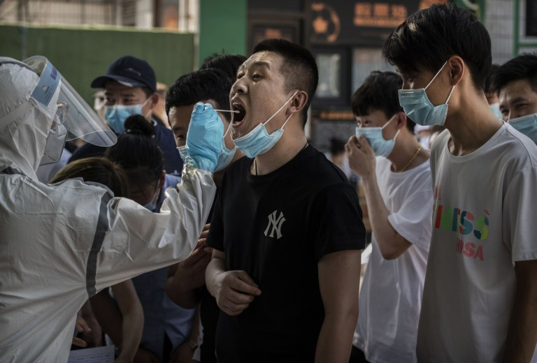 BEIJING, CHINA - JUNE 16: A Chinese man who has had any contact with the Xinfadi Wholesale Market or from someone who has, reacts as a Chinese control outbreaks worker performs a nucleic acid test for COVID-19 to a test center on the 16th of June 2020 in Beijing, China. The authorities are trying to contain the outbreak that has been linked to the Xinfadi wholesale market of power supply, Beijing is the largest supplier of products and meat. Several neighborhoods have been locked down and at least two other food markets were closed, as tens of thousands of people are invited to test for COVID-19 in the sites around the city. The epidemic, which has triggered fears of a second wave of infection after 56 days in a row and not at the national level of cases have been reported in the capital. More than 8 000 suppliers and the staff of the Xinfadi have already been tested, according to city officials, who are using the search for contacts to reach approximately 200 000 people have visited the market since the 30th of May. (Photo by Kevin Spawn/Getty Images)