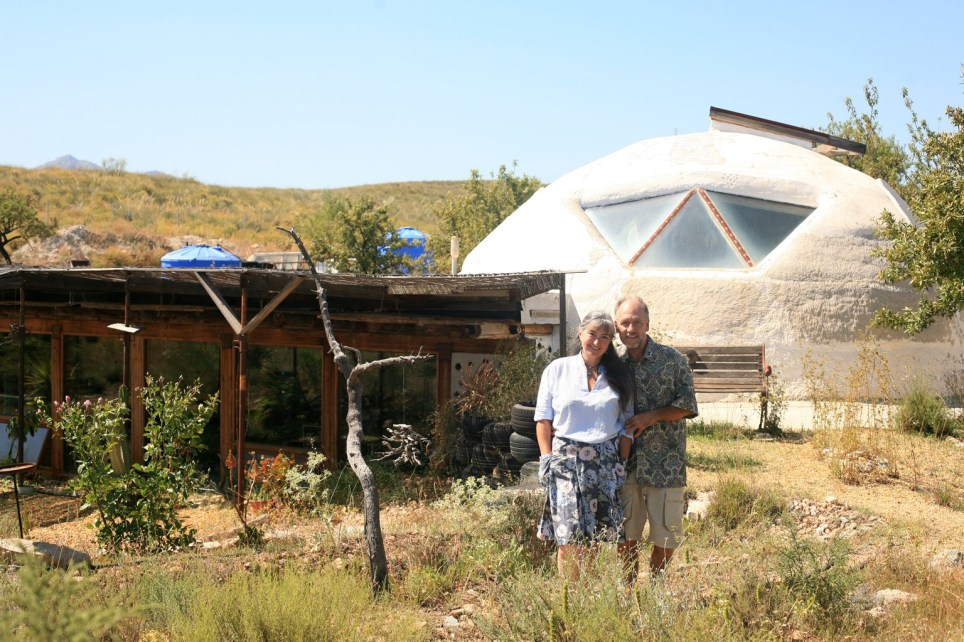Laura and Dave outside their Earthship home.