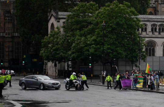 A protester from a pro-Kurdish demonstration is stopped and detained by police officers as he ran towards the car of Britain's Prime Minister Boris Johnson (L) as it was leaving with a police escort from the Houses of Parliament in London on June 17, 2020. - The protester ran into the road towards the Jaguar that normally carries the Prime Minister Boris Johnson and was stopped by police. As the Jaguar stopped it was subsequently struck from behind by the next vehicle in the convoy resulting in a large dent. (Photo by DANIEL LEAL-OLIVAS / AFP) (Photo by DANIEL LEAL-OLIVAS/AFP via Getty Images)