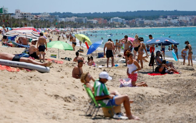 People sunbathe on Playa de Palma beach in Mallorca, as Spain officially reopens the borders amid the coronavirus disease (COVID-19) outbreak, in Palma de Mallorca, Spain June 21, 2020. REUTERS/Enrique Calvo