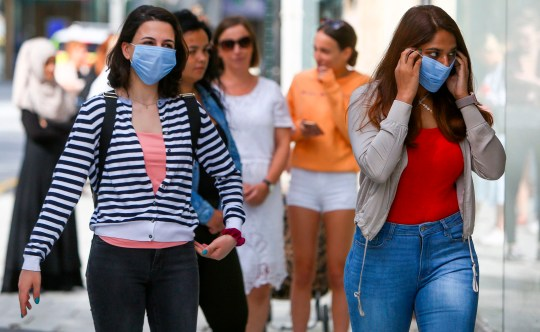 Shoppers, some wearing PPE (personal protective equipment), of a face mask or covering as a precautionary measure against spreading COVID-19, maintain the British government's current social distancing guidelines and stand two metres (2M) apart as they queue to enter a store in Cardiff on June 22, 2020, as some non-essential retailers in Wales are able to reopen from their enforced coronavirus shutdown. - Various stores and outdoor attractions in Wales are set to open Monday for the first time in nearly three months, as the government continues to ease its coronavirus lockdown, but pubs and restaurants must remain closed, and people must still stay 'local', where possible. (Photo by GEOFF CADDICK / AFP) (Photo by GEOFF CADDICK/AFP via Getty Images)