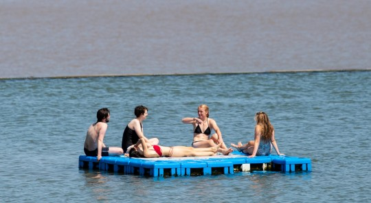 People enjoy the hot weather at Clevedon Marine Lake. Clevedon, Somerset. 23 June 2020.