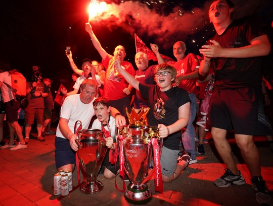 Liverpool supporters with replica Premier League and Champions League trophies as they celebrate outside of Anfield Stadium in Liverpool, England, Thursday, June 25, 2020 after Liverpool clinched the English Premier League title. Liverpool took the title after Manchester City failed to beat Chelsea on Wednesday evening. (AP photo/Jon Super)