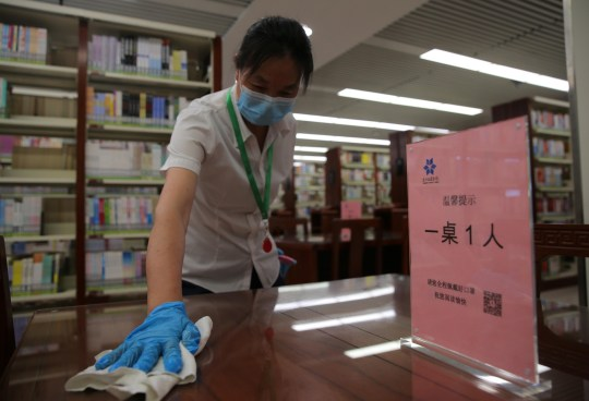 BEIJING, CHINA - JUNE 29: A staff member wearing face mask disinfects at the public area of Tongzhou District Library on June 29, 2020 in Beijing, China. (Photo by Yang Kejia/China News Service via Getty Images)