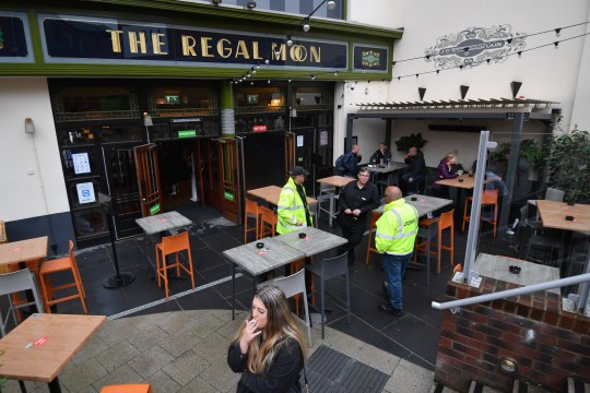 ROCHDALE, ENGLAND - JULY 04: Customers smoke in the beer garden at the Regal Moon JD Wetherspoons pub on July 04, 2020 in Rochdale, England. The UK Government announced that Pubs, Hotels and Restaurants can open from Saturday, July 4th providing they follow guidelines on social distancing and sanitising. (Photo by Anthony Devlin/Getty Images)