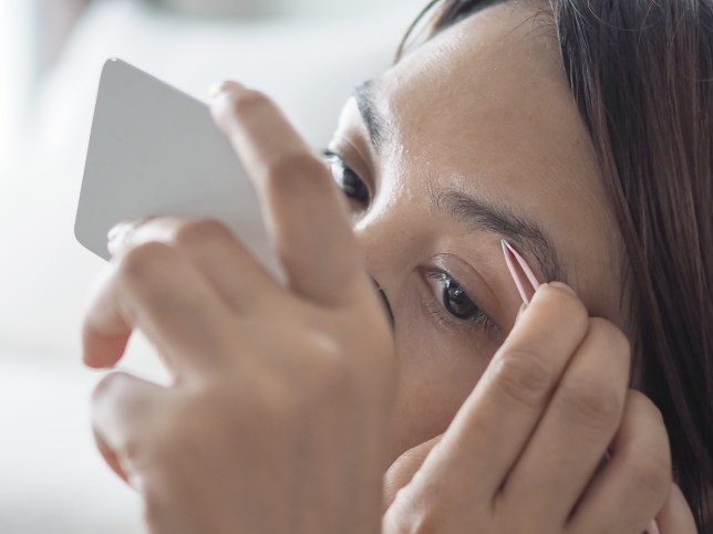 Close-Up Of Woman Removing Eyebrows