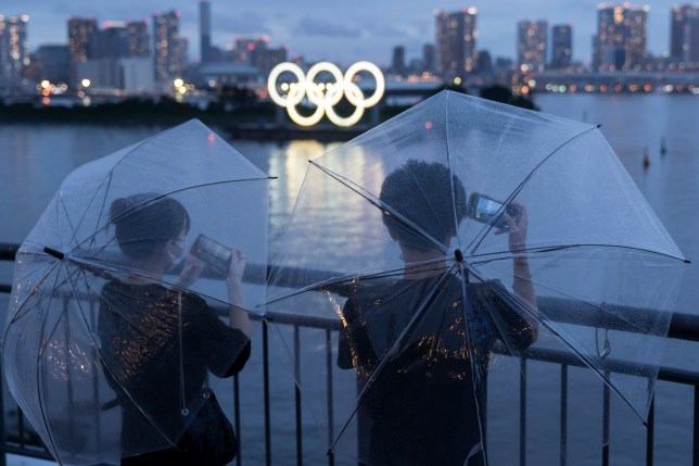 People take photographs of Illuminated Olympic rings at dusk on the day marking one year to go until the Tokyo Olympic Games in 2021.