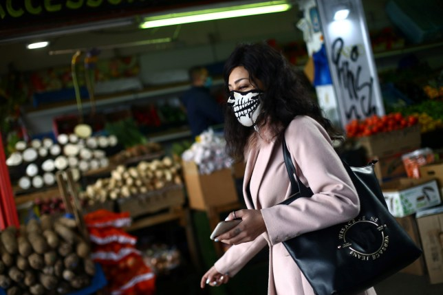 A woman is seen wearing a protective face mask in Peckham
