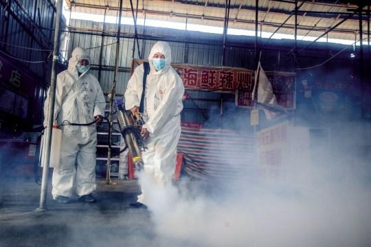 Cette photo prise le 6 mai 2020 montre des volontaires pulvérisant du désinfectant sur un marché à titre préventif contre le coronavirus COVID-19 alors qu'il s'apprête à rouvrir dans la ville frontalière de Suifenhe, dans le nord-est de la Chine, dans la province du Heilongjiang.
