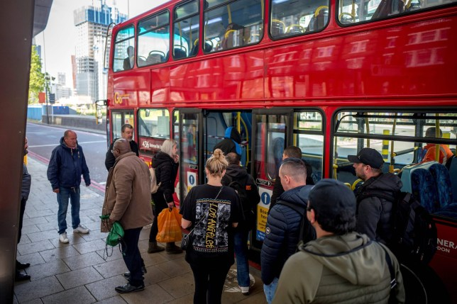 Commuters, some wearing PPE (personal protective equipment), including a face mask as a precautionary measure against COVID-19, wait to board a TFL (Transport for London) red London bus at Vauxhall bus station in central London on May 18, 2020.